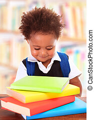 Little clever preschooler in the library, reading books,...