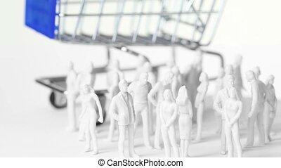 Little colorless toy men and women stand in front of big shopping trolley