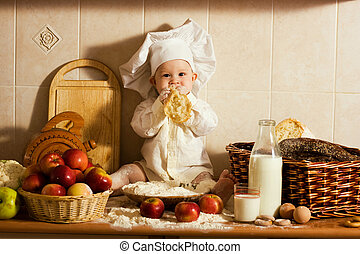 little boy in the cook costume at the kitchen with bread