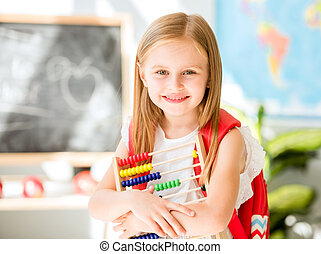 Little counting on the colourful abacus in the school classroom