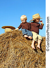 Little Country Boys Sitting on Hay Bale