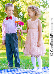 little couple in love on a meadow with a bouquet of flowers