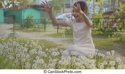 Little curly and more girl blowing dandelion and more slow...