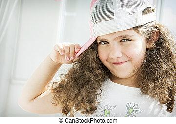 Little curly girl in a cap.