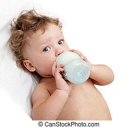 little curly-headed baby sucks a bottle of milk