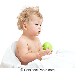 little curly-headed child holding a green apple on white backgro