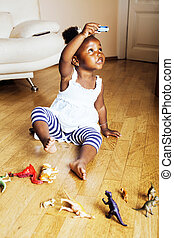 little cute african american girl playing with animal toys...