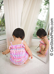 Little cute asian baby girl playing near mirror at home