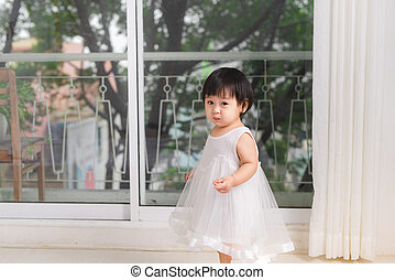 Little cute asian baby girl playing near the window at home