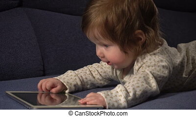 Little cute baby girl playing with touchpad and learning how...