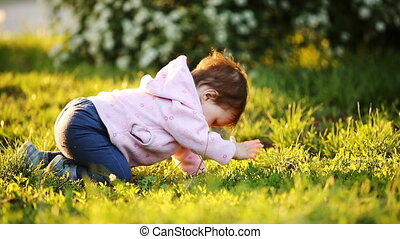 Little cute baby learning to crawl on the green grass in the park at sunset.