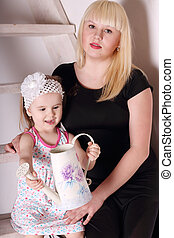 Little cute blond girl in dress sitting on wooden stairs with her mother