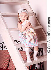 Little cute blond girl in dress sitting on wooden stairs