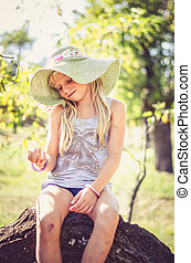 little cute blond girl in hat sitting in tree trunk