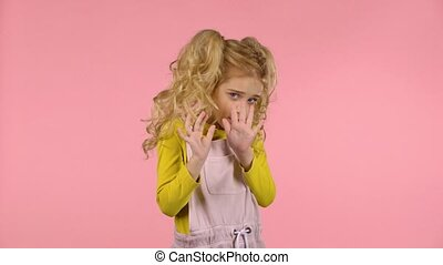 Little cute blond girl is scared and hiding - Little cute...