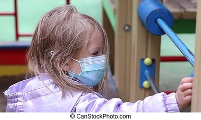 little cute blonde girl in a medical blue mask on the playground. covid 19 pandemia. kids on isolation. FullHD footage
