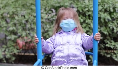 little cute blonde girl in a medical blue mask rides a swing on the playground. covid 19 pandemia. kids on isolation. FullHD footage