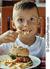 little cute boy 6 years old with hamburger and french fries ...