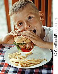 little cute boy 6 years old with hamburger and french fries...