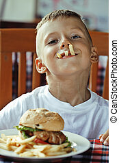 little cute boy 6 years old with hamburger and french fries