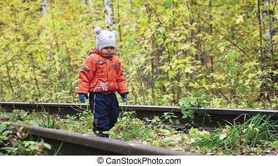 Little cute boy carefree walks along railway in slow motion....