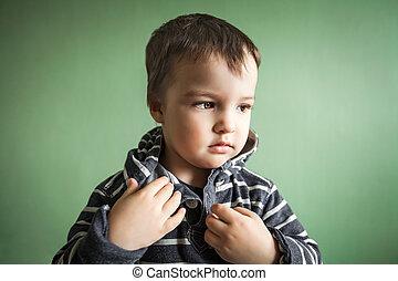 Little cute boy fastening collar of pullover