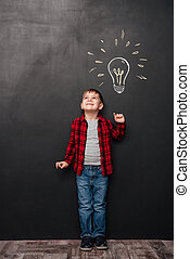 Little cute boy having an idea over chalkboard background