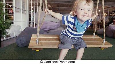 Little cute boy having fun on swings