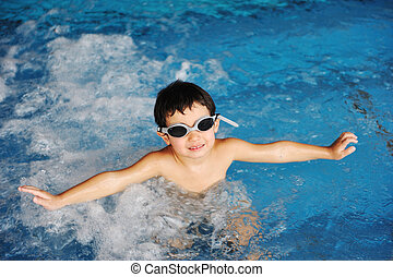 Little cute  boy in blue water of the swimming pool, summer time for fun