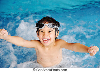 Little cute boy in blue water of the swimming pool, summer...