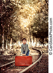 little cute boy in vintage clothes standing on an abandoned railroad with a vintage suitcase in his hands