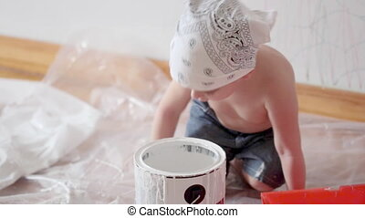 little cute boy kid dunks finger in paint can painting wall at home
