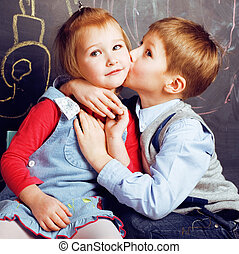 little cute boy kissing blonde girl in classroom at...