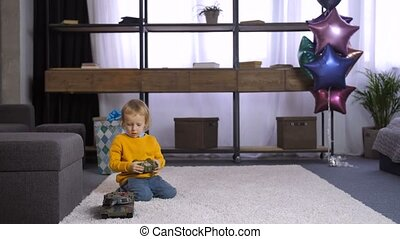 Little cute boy learning to use remote control toy