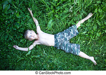 Little cute boy lying on the grass, top view.