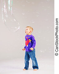 Little cute boy playing a soap bubbles