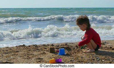 Little cute boy playing on the beach with sand