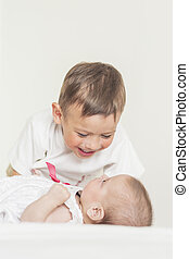 Little Cute Boy Playing with His Infant Sister and Smiling. Again