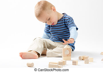 Little cute boy playing with wooden building blocks. Isolated on white.