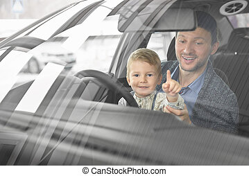 Little cute boy posing with father in car cabin.