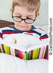 Little cute boy reading book in bed