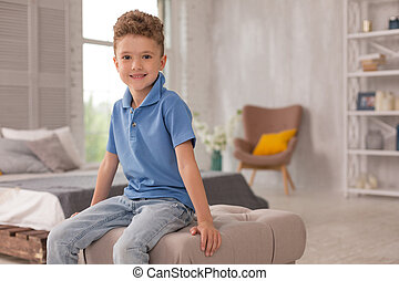 Cute boy. Little pleasant looking cute boy wearing dark blue shirt and denim jeans sitting on hassock in the living room