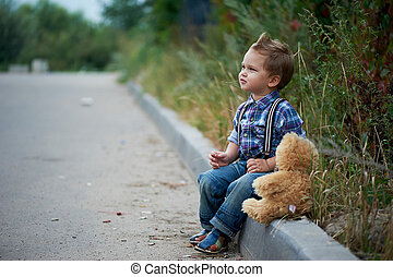 Little cute boy sitting on the sidewalk and talking with Teddy . Memories of childhood carefree