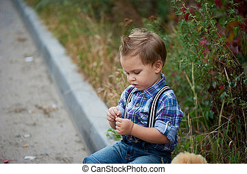 Little cute boy sitting on the sidewalk . Memories of childhood and carefree