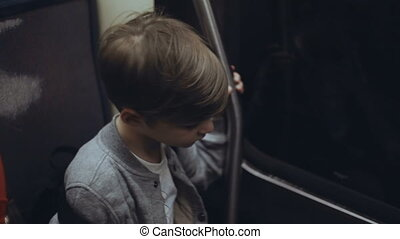 Little cute boy traveling through the city buy subway....