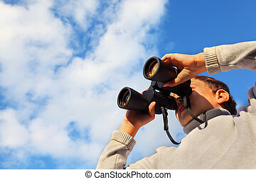 Little cute boy with binoculars outdoor; blue sky with white clouds