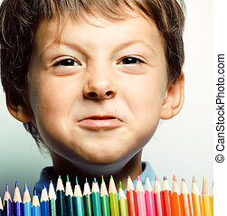 little cute boy with color pencils close up smiling, education face colored