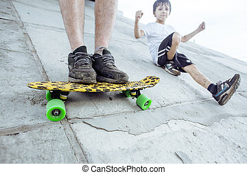 little cute boy with his father on skateboard learning to skate