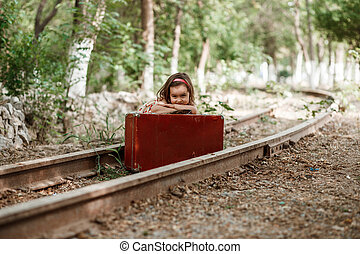 little cute Caucasian girl in vintage clothes with vintage suitcase on abandoned railway