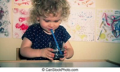 Little cute child blow air through straw into glass with...